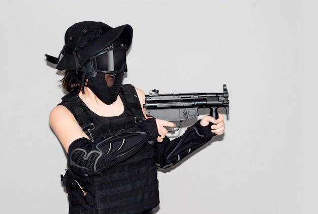 Aziatische dame in zwarte soldaat bb pistool sport spel kostuum en wapen