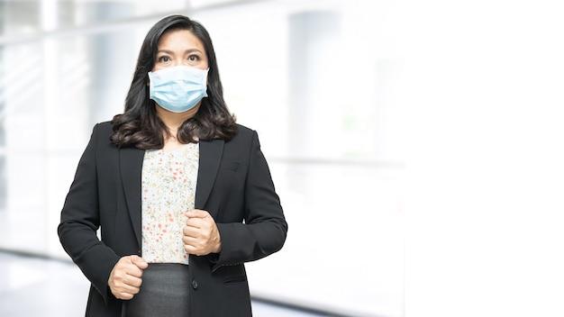 Aziatische dame met masker nieuw normaal op kantoor om veiligheidsinfectie covid19 coronavirus te beschermen