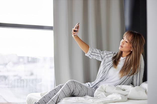 Aziatische dame selfie maken op smartphone, genieten van het weekend, foto naar iemand sturen, zittend op bed