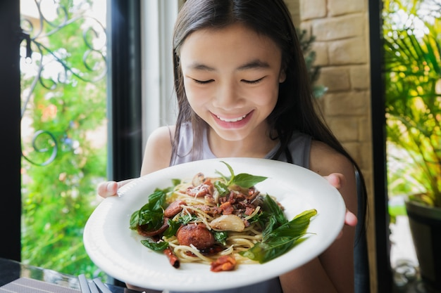 Aziatische dame toont spaghetti met thais voedselbovenste laagje in restaurant