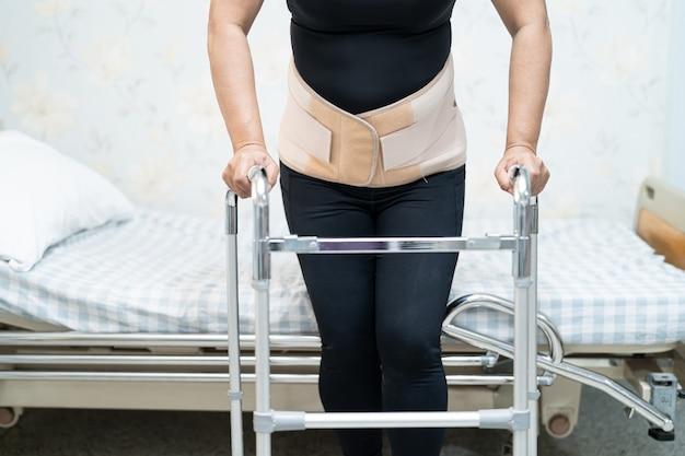 Aziatische damepatiënt die de steunriem van de rugpijn voor orthopedische lumbaal met rollator draagt