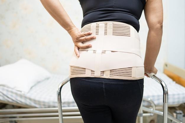 Aziatische damepatiënt die de steunriem van de rugpijn voor orthopedische lumbaal met rollator draagt.