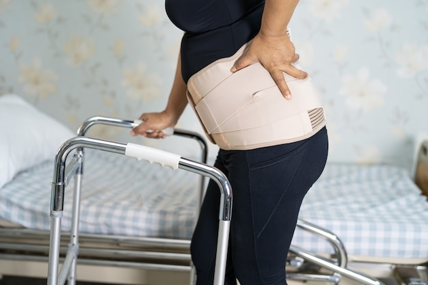 Aziatische damepatiënt die steunriem voor rugpijn draagt voor orthopedische lumbale met rollator.