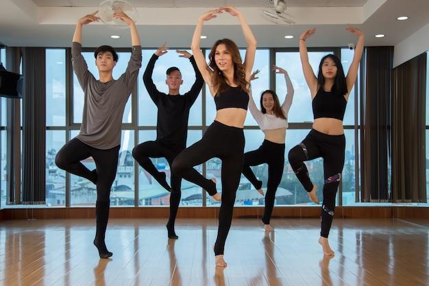 Aziatische dansers die zich op één voet bevinden