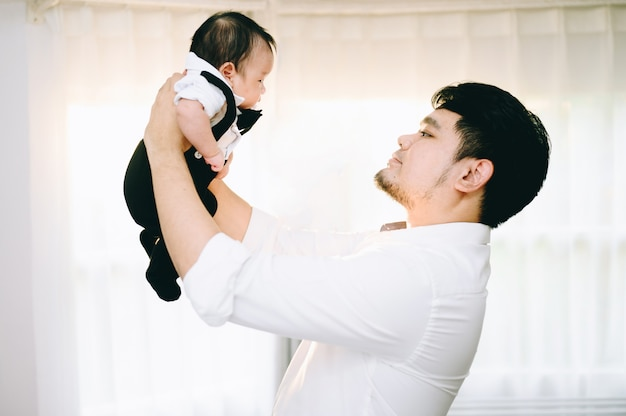 Aziatische de babyzoon van de vaderholding omhoog in de lucht thuis.