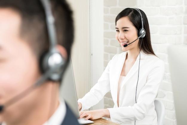 Aziatische de dienstagent die van de vrouwenklant in call centre werkt