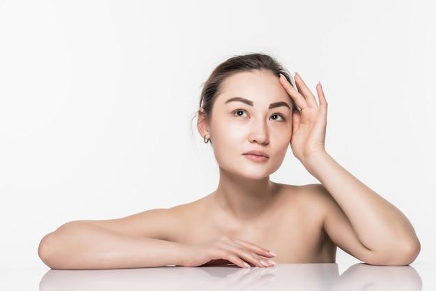 Aziatische de huidzorg van de schoonheidsvrouw die op witte muur wordt geïsoleerd