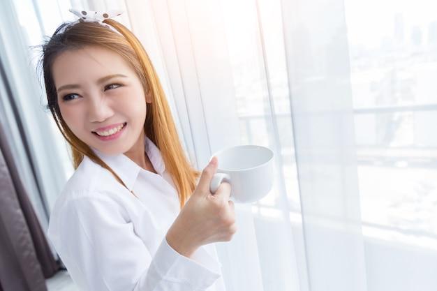 Aziatische de levensstijlglimlach van de vrouwen gelukkige ochtend met koffie naast het venster.