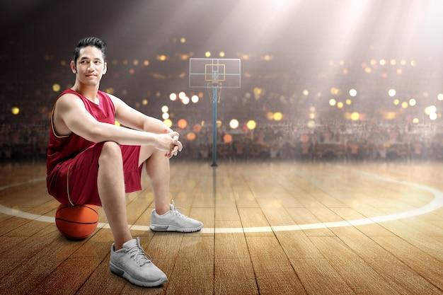 Aziatische de spelerzitting van het mensenbasketbal op de bal