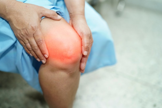 Aziatische de vrouwen geduldige aanraking van de leeftijdsvrouw en voelt pijn haar knie: gezond medisch concept.