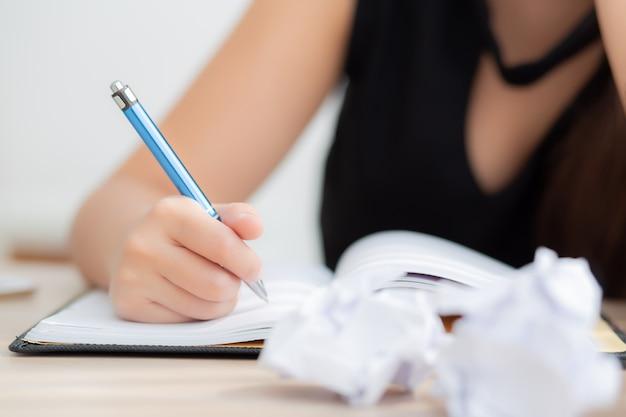 Aziatische de vrouwenschrijver van de close-uphand het denken idee en het schrijven op notitieboekje