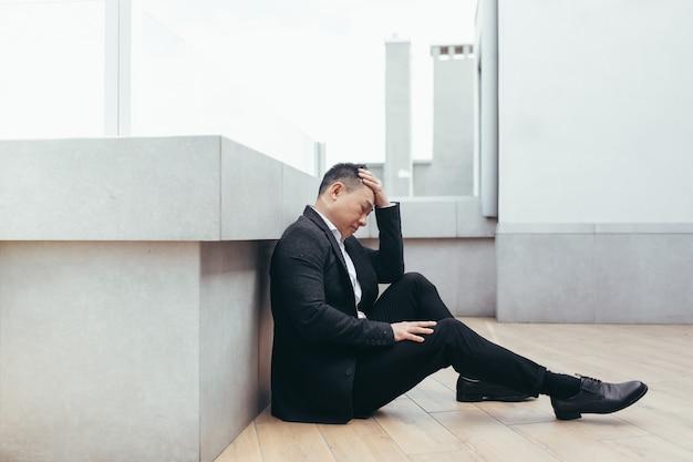 Aziatische depressieve man zit op straat buiten in de buurt van kantoorgebouw