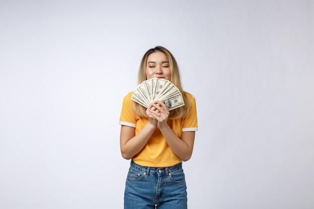 Aziatische die het contant geldnota's van de vrouwenholding op witte achtergrond worden geïsoleerd