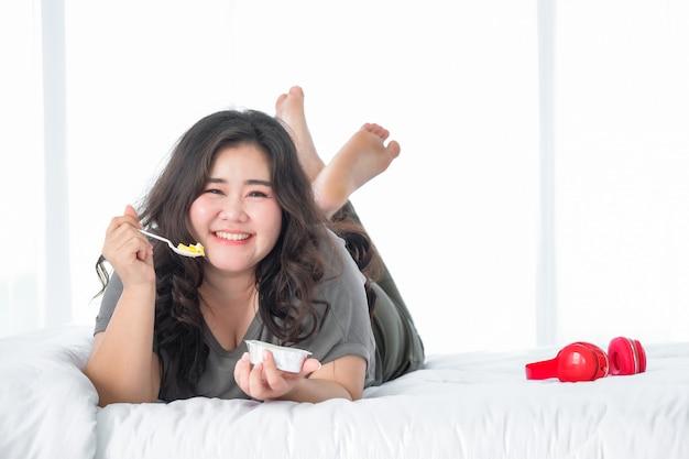 Aziatische dikke vrouw die van het eten van oranje cake op bed geniet