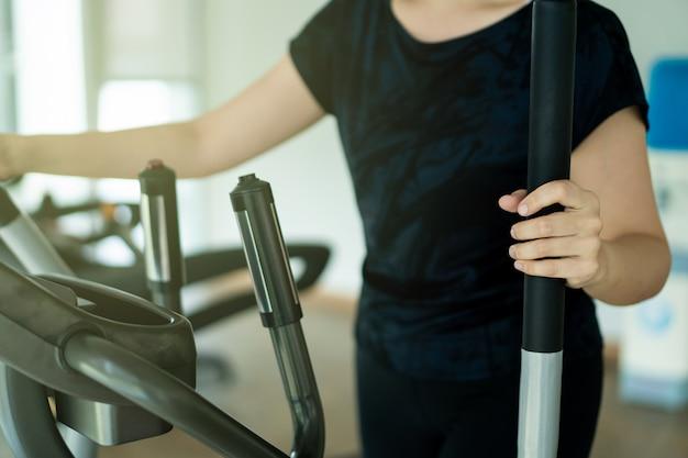 Aziatische dikke vrouw met behulp van fitnessapparaten in indoor gym.