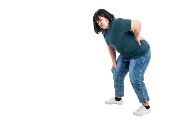 Aziatische dikke vrouw met knie- en taillepijn als gevolg van overgewicht op een witte geïsoleerde achtergrond