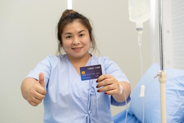Aziatische dikke vrouw verblijf in het ziekenhuis en het tonen van een creditcard met duim omhoog, financiële steun in de medische en gezondheidszorg