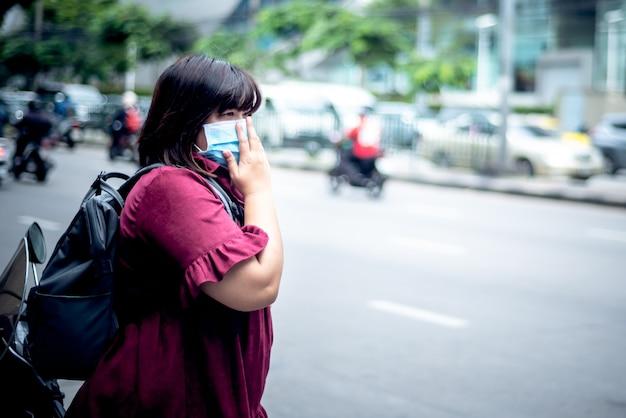 Aziatische dikke vrouwentoerist die een chirurgisch masker draagt om pm 2.5-stof of virus te voorkomen, staan en wachten op de bus langs de weg, voor mensen en gezondheidszorgconcept.