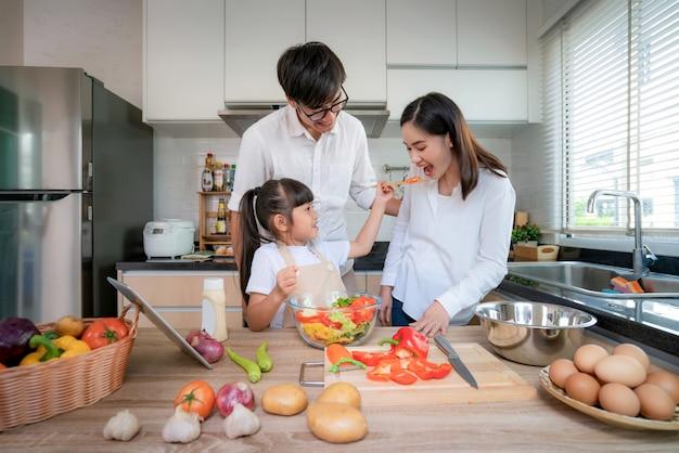 Aziatische dochters die salade voeden aan haar moeder en haar vader staan klaar wanneer een gezin thuis in de keuken kookt. gezinsleven liefdesrelatie, of thuis plezier vrijetijdsactiviteit concept