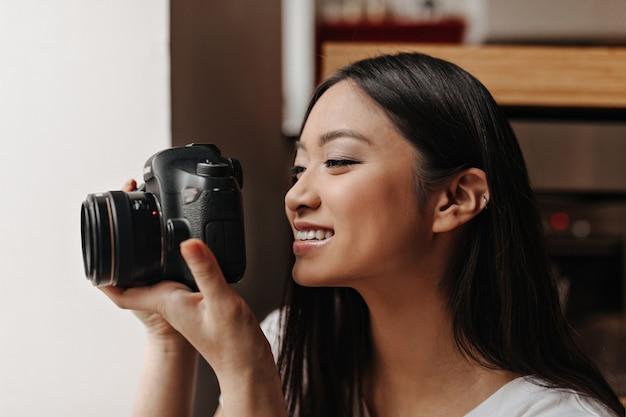 Aziatische donkerharige vrouw met glimlach maakt foto op zwarte voorkant