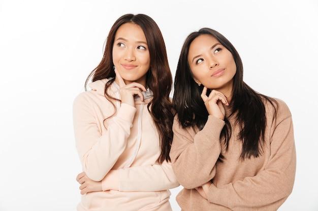 Aziatische doordachte positieve dameszussen. opzij kijken.