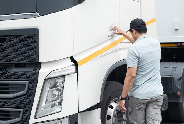 Aziatische een vrachtwagenchauffeur is klaar om semi-vrachtwagen te rijden