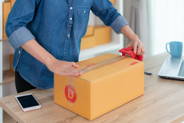 Aziatische eigenaar zakenvrouw werken thuis voor online winkelen, inpakken producten