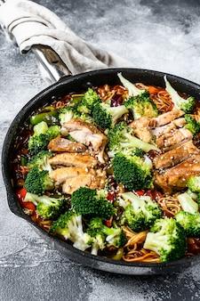 Aziatische einoedels met groenten en vlees bij het koken van pan. grijze achtergrond. bovenaanzicht