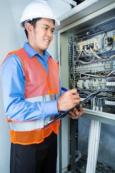 Aziatische elektricien bij paneel op bouwwerf
