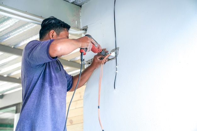 Aziatische elektricien probeert swicht en elektrische draad op de vernietigde muur te repareren.