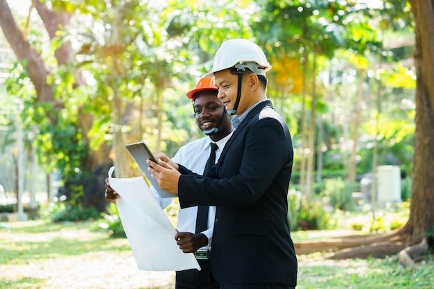 Aziatische en afrikaanse architecteningenieur twee deskundigheidenteamplan met glimlach in groene aard.