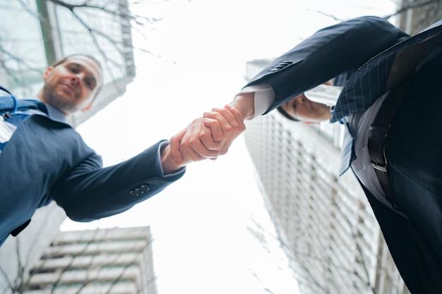 Aziatische en blanke zakenmensen handen schudden in pakken