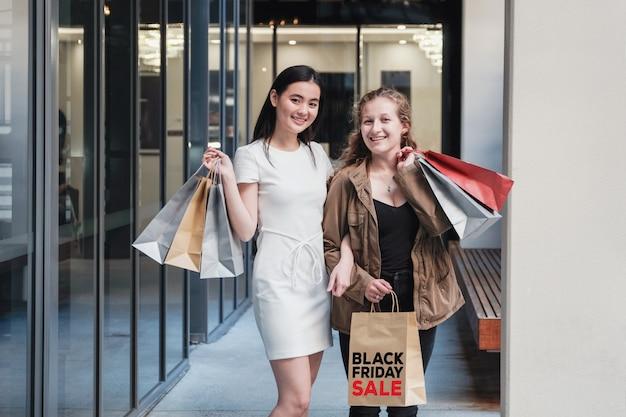 Aziatische en caucasion gemengd ras jonge vrouwen met boodschappentassen,