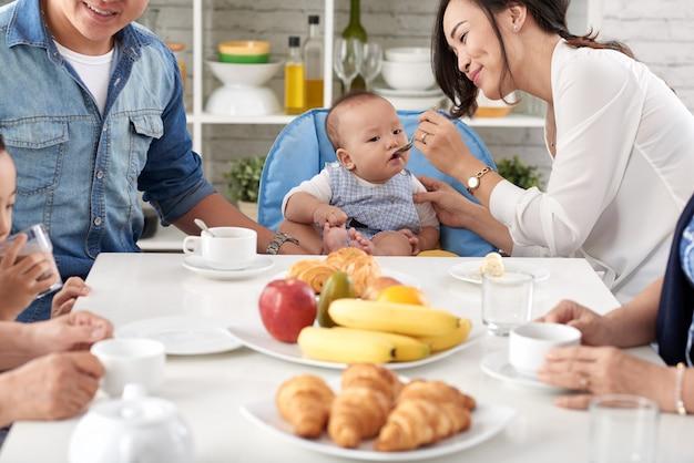 Aziatische en gelukkige familie bij het ontbijt