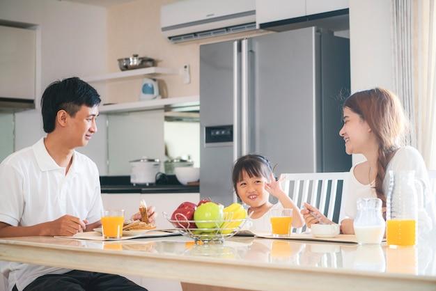 Aziatische en gelukkige familie die heerlijk ontbijt samen in de keuken thuis hebben.