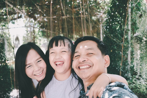 Aziatische en gelukkige familie die selfie in het park nemen