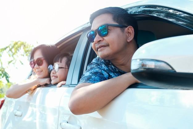 Aziatische en gelukkige familie die zonnebril draagt en in de auto zit die uit vensters kijkt