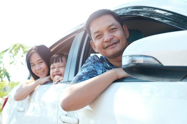Aziatische en gelukkige familie zitten in de auto die uit vensters kijkt