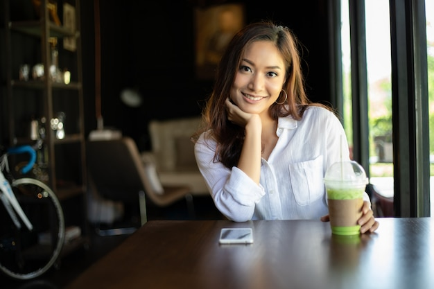 Aziatische en gelukkige vrouwen die glimlachen ontspannen in een koffie