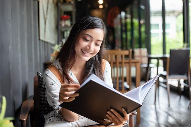 Aziatische en vrouwen die en het gelukkige ontspannen lezen ontspannen in een koffiewinkel na het werken in een succesvol bureau.