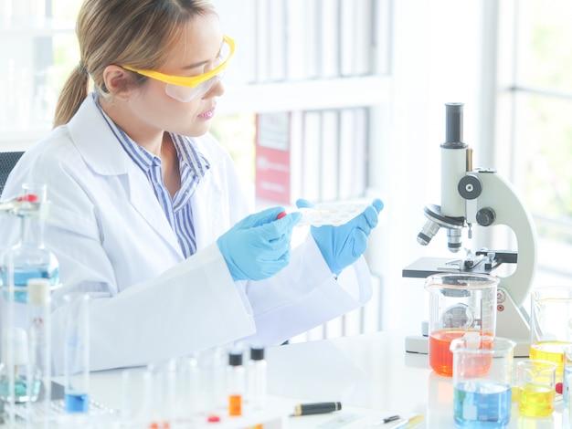 Aziatische ernstige vrouwelijke chemicus die in laboratorium werkt
