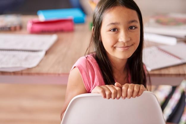 Aziatische etniciteit meisje, zittend op de stoel