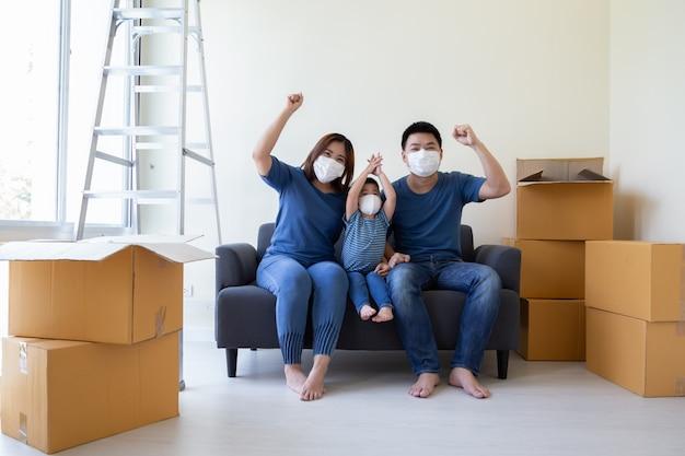 Aziatische familie die beschermend medisch masker draagt om virus covid-19 te voorkomen en hand tijdens bewegende dag en verhuizing bij nieuw huis. verhuizen en nieuw onroerend goed concept