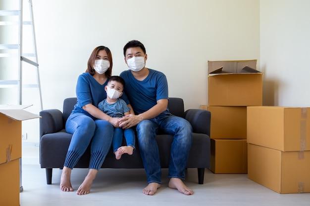 Aziatische familie die beschermend medisch masker draagt om virus covid-19 te voorkomen tijdens het verplaatsen van dag en verhuizen naar nieuw huis. verhuizen en nieuw onroerend goed concept