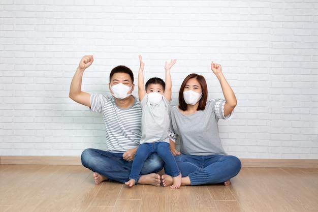 Aziatische familie die beschermend medisch masker draagt voor het voorkomen van virus covid-19 en hand omhoog en samen op vloer zit thuis. familiebescherming tegen verontreinigd luchtconcept
