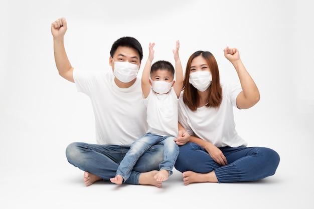 Aziatische familie die beschermend medisch masker draagt voor het voorkomen van virus wuhan covid-19 en hand omhoog en samen zittend op vloer geïsoleerde witte muur. familiebescherming tegen verontreinigd luchtconcept