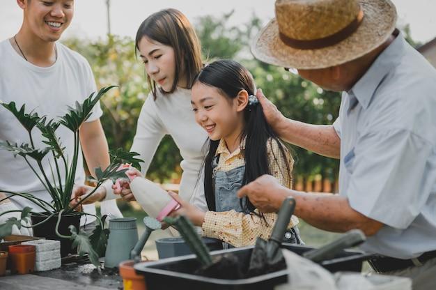 Aziatische familie die boom in tuin thuis plant. ouder met kind en grootvader levensstijl.
