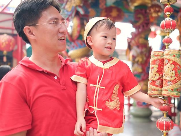 Aziatische familie die chinees nieuw jaar, leuk weinig 2 jaar oud kind van de peuterjongen in traditioneel rood chinees kostuum viert bij lokale chinese tempel met zijn vader