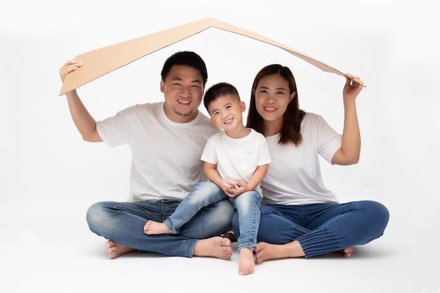 Aziatische familie die en huis glimlachen spelen door pakpapier op geïsoleerde witte muur. nieuw huis jong familieconcept