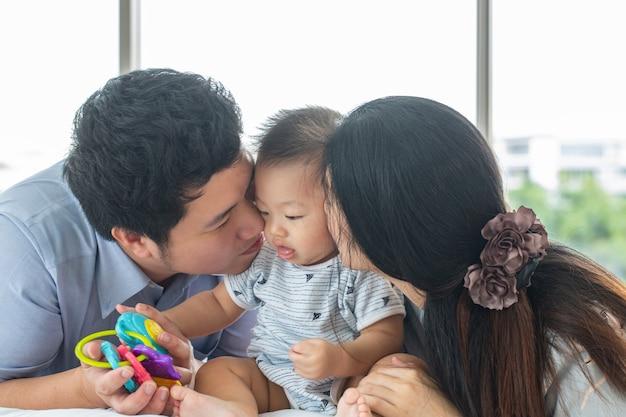Aziatische familie die hun baby in huis kust.
